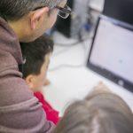 Monitor con alumnado en aula de informático¡a